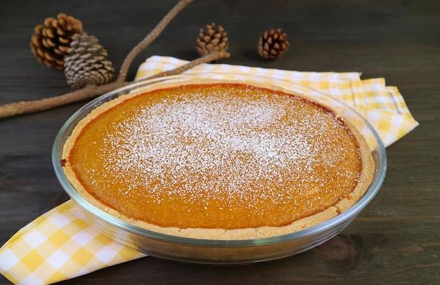 Восхитительный домашний тыквенный пирог, посыпанный сахарной пудрой, на деревянном столе