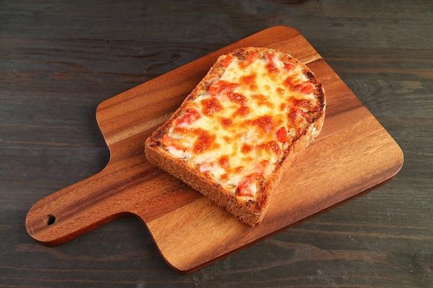木製のブレッドボードでおいしい自家製トマトとチーズのピザトースト