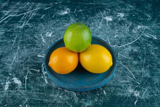 Восхитительные лимоны на деревянной тарелке, на мраморном фоне. фото высокого качества