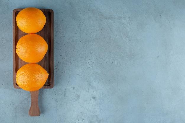 Восхитительные апельсины на доске, на мраморном столе.