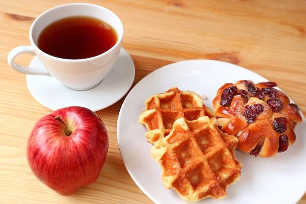 Восхитительная выпечка с чашкой горячего чая и свежим яблоком для здорового завтрака