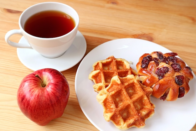 Delectable pastries with a cup of hot tea and fresh apple for a healthy breakfast