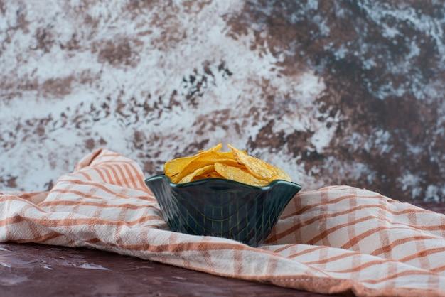 Deliziose patatine in una ciotola su un canovaccio, sul tavolo di marmo.