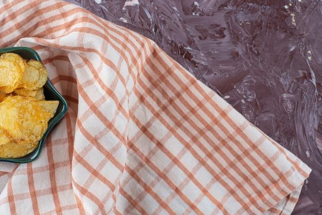 大理石のテーブルの上に、ティータオルの上にボウルに入れておいしいポテトチップス。