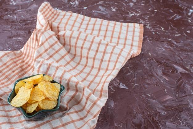 대리석 탁자 위에 있는 차 타월에 있는 그릇에 맛있는 감자 칩.