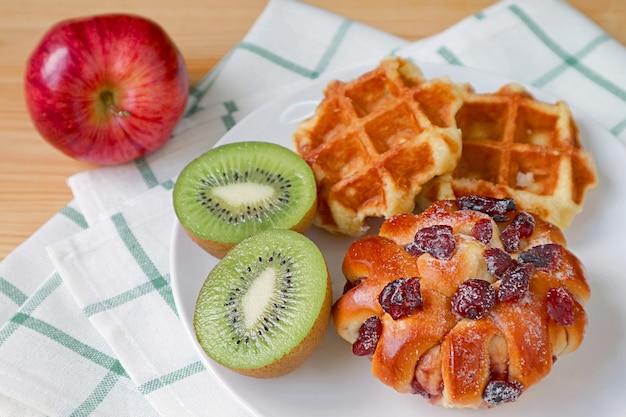 ヘルシーな朝食に新鮮なフルーツを添えたおいしいレーズンパンとベルギーワッフル