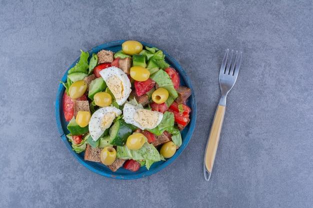 大理石の表面に朝食の材料とおいしいサラダミックス