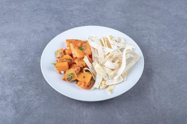 Lavash affettato delizioso e carota al forno nel piatto, sulla superficie di marmo.