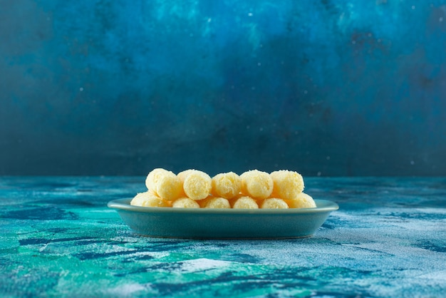 青いテーブルの上に、おいしいスイートコーンが皿に刺さっています。