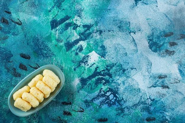 Deliziosi bastoncini di mais dolce in un piatto, sul tavolo blu.