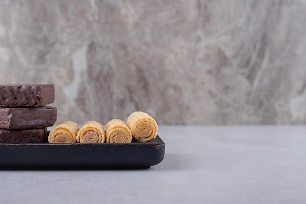 Deliziosi rotoli di wafer e wafer ricoperti di cioccolato su un piatto di legno sul marmo.