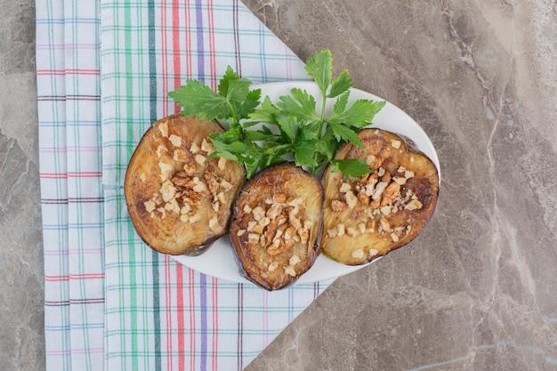 Piatto delizioso di melanzane indiane fritte a fette guarnito con aglio e prezzemolo tritati, su marmo.