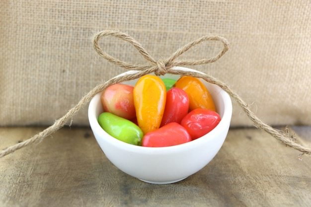 Deletable imitation fruits (kanom look choup) in white small bowl on wood table and sack background.