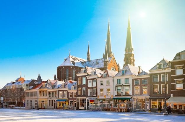 冬の雪に覆われた晴れた日にデルフトのメイン広場