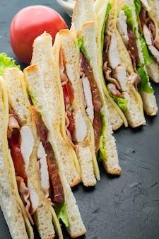 黒の背景に、鶏肉と新鮮なサンドイッチをデリ