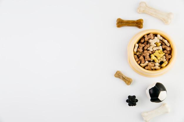Деликатес и игрушки для собак на белой поверхности