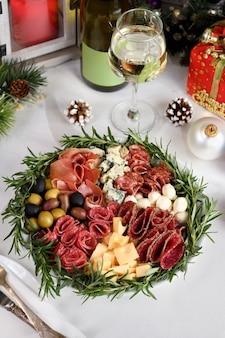 Деликатесное ассорти из закусок из салями и сырных ветчин с оливками анти-сервировка на рождество