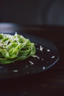 Delicacy green pasta with homemade spinach and broccoli under a parmesan cheese and sesame seeds