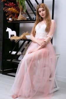 우아한 내실 드레스에 의자에 앉아 섬세하고 섹시한 아름다운 소녀