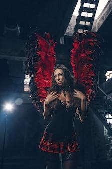 繊細な美しいブルネットの女性が赤い暗い天使の羽でポーズします。スタジオ撮影。
