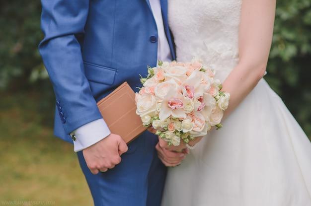 花嫁の手にピンクの牡丹のバラと蘭の繊細な美しいウェディングブーケ
