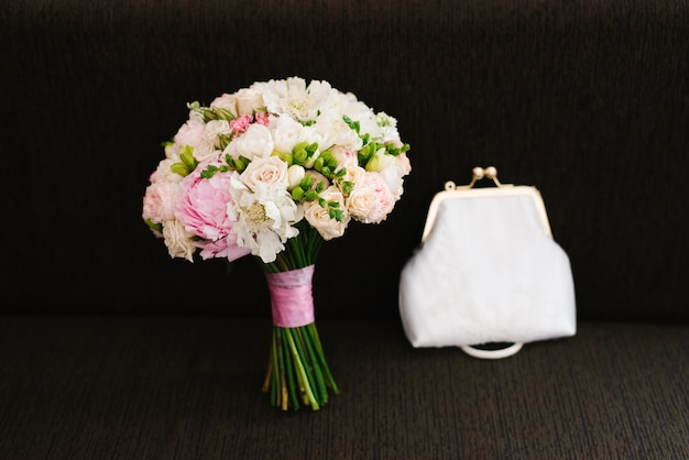 A delicate and beautiful wedding bouquet and white bag on a dark brown background. accessories bride at the wedding