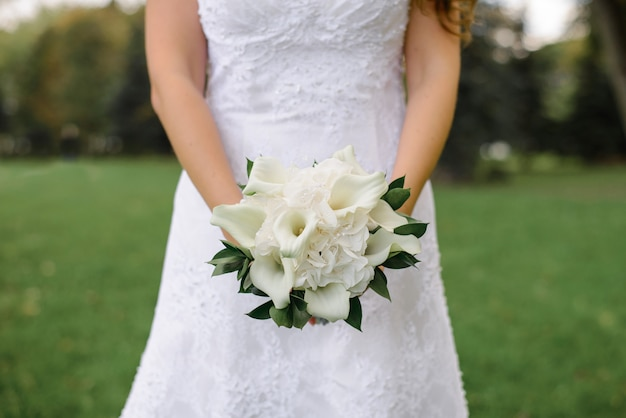 Delicate beautiful white wedding bouquet of calla and hydrangea with greenery in the hands of the bride