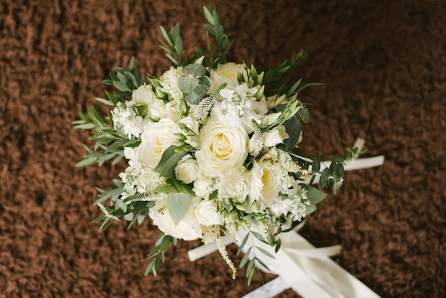 Delicate beautiful white wedding bridal bouquet on brown
