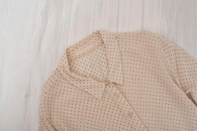 Нежная бежевая блузка на деревянном фоне