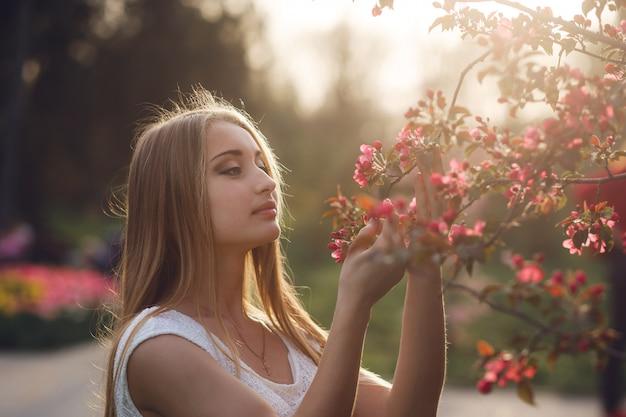 Нежная блондинка девушка держит цветущие ветви сакуры в вечернем солнечном свете