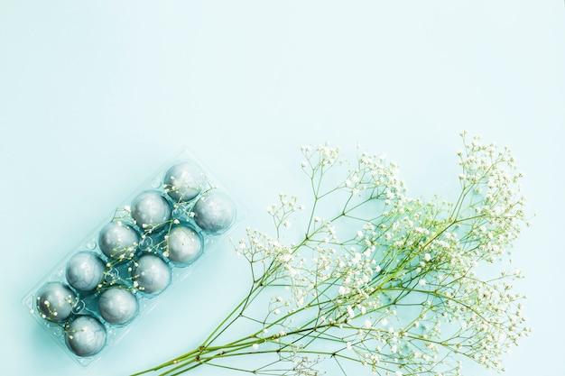 Delicate blue easter eggs among the flowers of gypsophila on a blue background.
