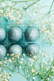Delicate blue easter eggs among the flowers of gypsophila on a blue background