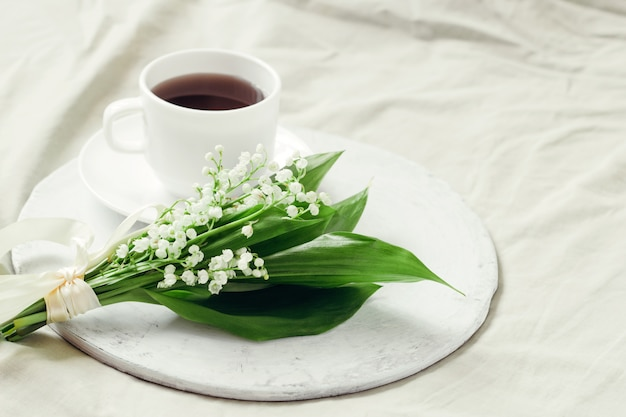 Delicate bouquet of fresh lilies of the valley decorated with silk ribbon and freshly brewed coffee