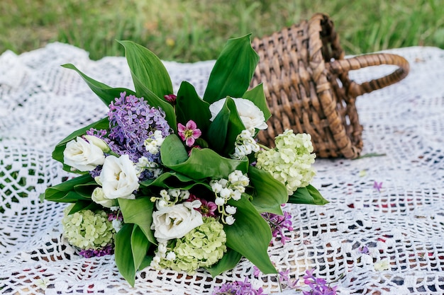 Delicate bouquet of lilac, lily of the valley, eustoma, viburnum and saxifrage.