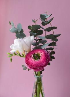 Нежный букет из ярко-розового цветка ранункулюса и белой фрезии с веточками эвкалипта на розовой поверхности