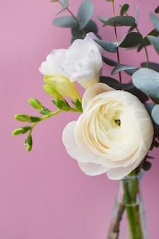 Нежный букет из нежных розовых цветов ранункулюса и белой фрезии с веточками эвкалипта на розовой поверхности