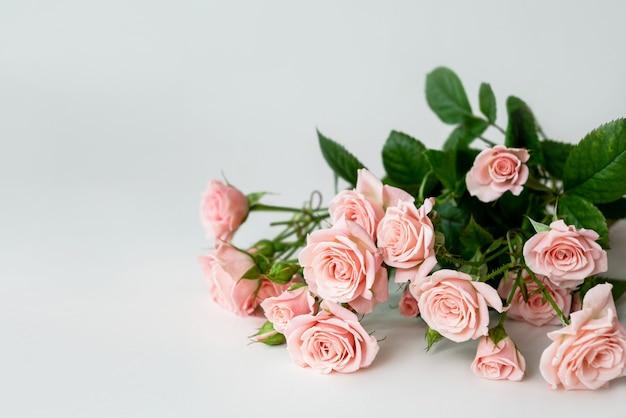 明るい背景にピンクのバラの繊細な花束