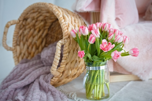 고리 버들 바구니와 핑크 튤립의 섬세 한 꽃다발.