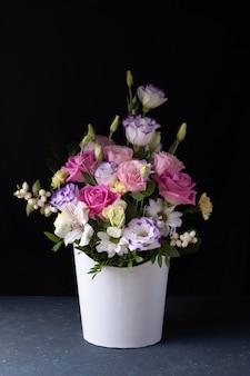 Нежный букет из роз, лизиантусов, ромашек, хризантем, неоткрытых бутонов в белой круглой коробке.