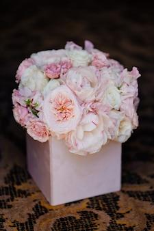 箱に入った白とピンクのバラの繊細な花束。インテリア用の花の構成と女性への贈り物。