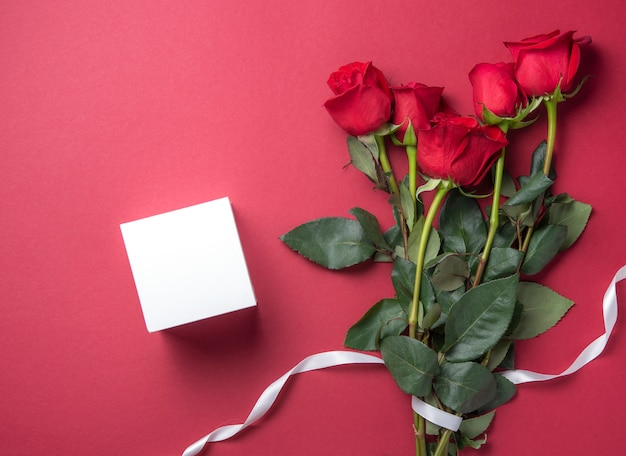 Delicate bouquet of red roses lies on a red background with white pure box present. valentines day