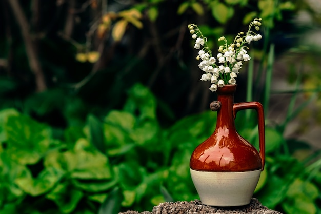 A delicate bouquet of white lilies of the valley in a brown glossy clay small jug on which a small snail crawls