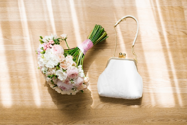 Delicate bridal bouquet and white handbag on beige wooden wall