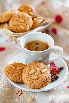 カリカリの新鮮な松の実とコーヒーカップが入った繊細なバタービスケット
