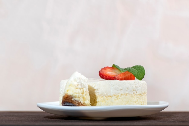 Delicate cheesecake with fresh strawberries on white plate
