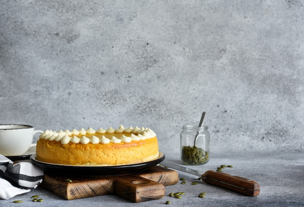 Delicate cheesecake with pumpkin on a wooden board on a concrete background