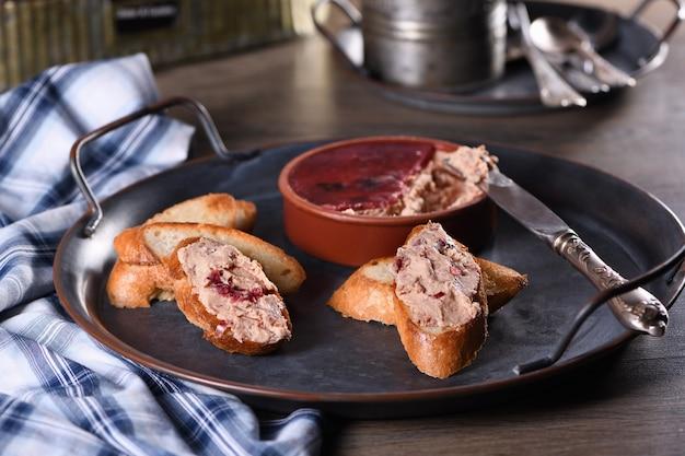 구운 바게트 조각에 으깬 크랜베리를 뿌린 섬세한 치킨 페이트. 컨트리 스타일의 음식.