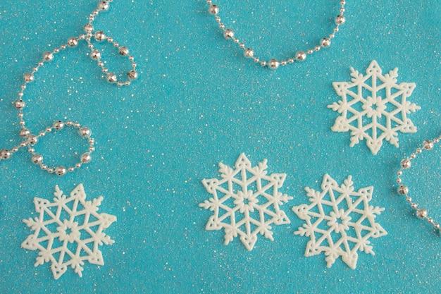 Нежная новогодняя композиция из белых снежинок на синем фетровом фоне с блестками копией пространства
