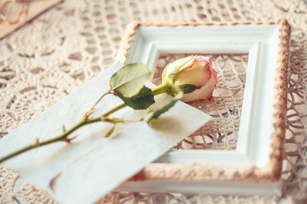Delicate composition of roses and photo frames decorated in rust