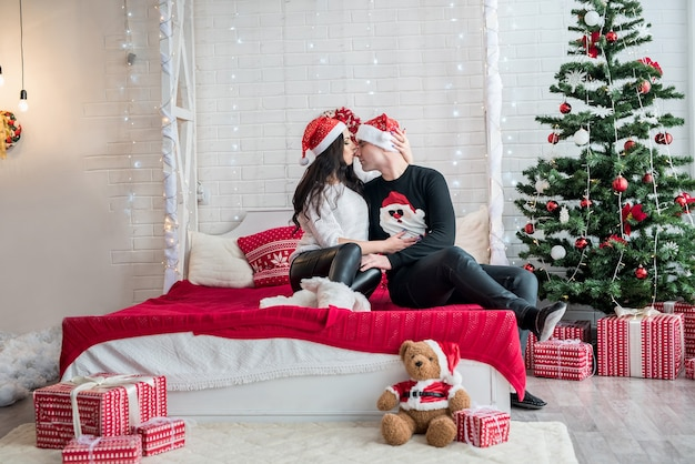 ベッドの上のクリスマススタジオでポーズをとる繊細なカップル